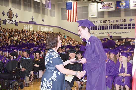 Senior Carter Stein, right, receives his diploma from District 877 school board member Amanda Reineck at the Buffalo High School graduation ceremony last Friday, June 7, in the Buffalo High School gym. There were 471 graduates in the Class of 2019...