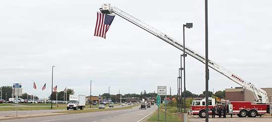 The Buffalo Fire Dept. displayed a large American flag on Friday, September 11 to remember those lost during the 9/11 terrorist attacks in 2001. Using one of their fire trucks, the flag proudly flew over Hwy. 55. Many vehicles driving by honked in...