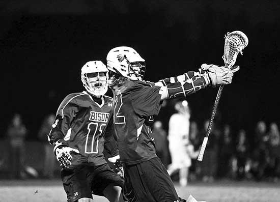 Noah VanderKooi (front) and Tyler Bruder (left)  of the Buffalo boys' lacrosse team celebrate one of VanderKooi's three goals in a thrilling 7-5 road win on April 25, 2014 at Providence Academy. The Bison trailed the Lions 5-2 midway through the...