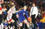 STMA's Mackenzie Kramer (right) dribbles by a defender in a 67-58 state quarterfinal victory over Lakeville North. In the background is Head Coach Kent Hamre. (Photo by Rob LaPlante)